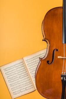 黄色の背景に弦と音楽のノートブックを持つ木製のバイオリン