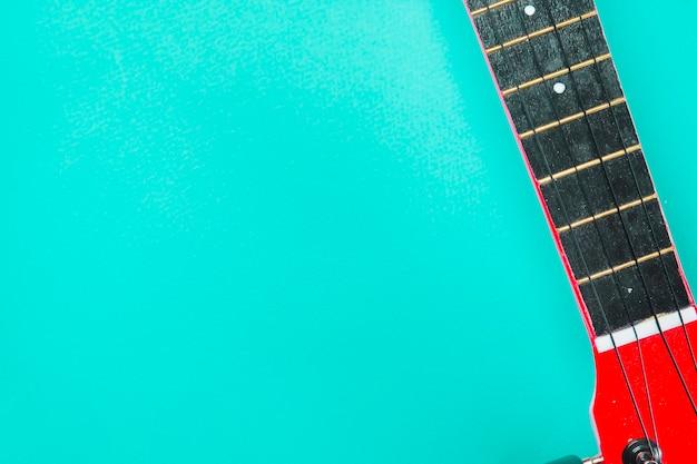 ターコイズブルーの背景に赤いアコースティッククラシックギターのクローズアップ