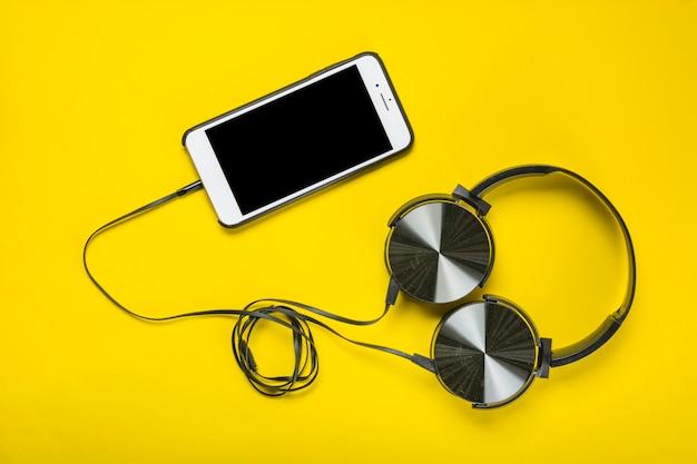黄色の背景に携帯電話で接続されたヘッドフォンのオーバーヘッドビュー