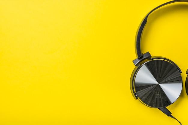 黄色の背景にヘッドフォンのオーバーヘッドビュー