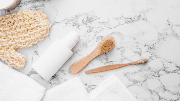 タオル;スクラブ手袋;大理石の背景にブラシと化粧品のボトル