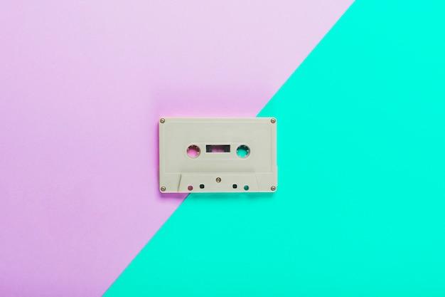 デュアルパープルとターコイズブルーの背景にカセットテープ
