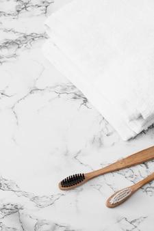 Деревянная зубная щетка и белые полотенца на мраморной поверхности