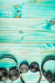 ターコイズの木製のテーブルの上にある黒いヘッドフォン