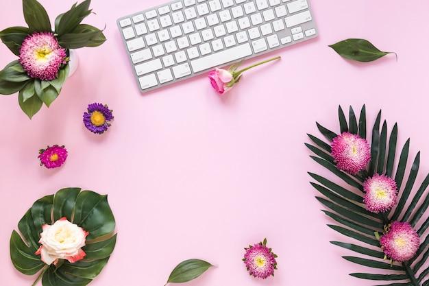カラフルな花とキーボードのピンクの背景の高い角度のビュー