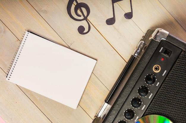 スパイラルメモ帳のオーバーヘッドビュー。木製の机の上に音符とアンプ