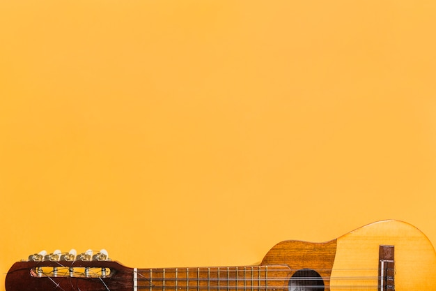 黄色の背景にウクレレのクローズアップ