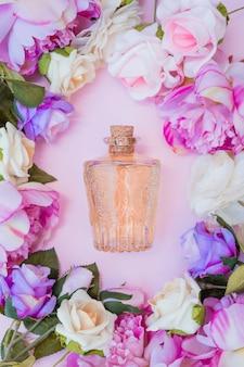 ピンクの背景に新鮮な花に囲まれたエッセンシャルオイルボトル