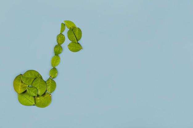 青い背景に緑の葉で作られたミュージカルノート