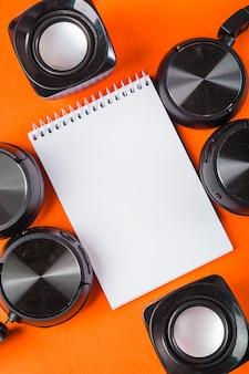 オレンジ色の背景にヘッドフォンとスピーカーと空白の白い螺旋のメモ帳