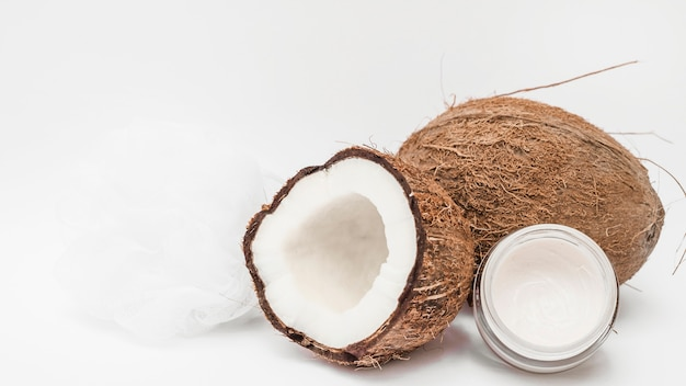 Увлажняющий крем; люфа и кокос на белой поверхности