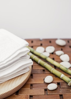白いタオル;木の表面に竹植物と小石