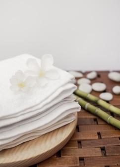 白い花と木製のトレイに積み重なったタオル