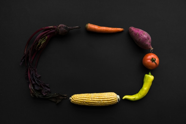 ビートルート;にんじん;スイートポテト;トマト;緑色の唐辛子、コーンコブ、黒背景にフレームを形成