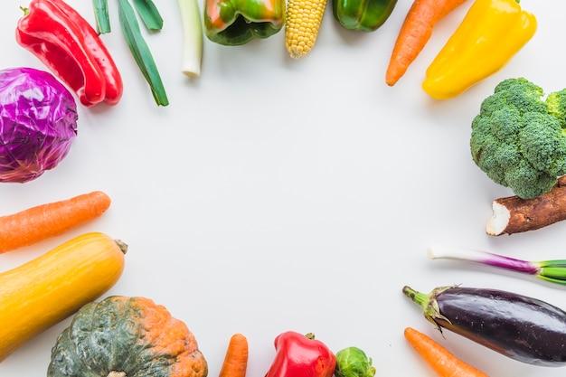 白い背景に円形のフレームを形成する様々な生野菜の高い角度のビュー