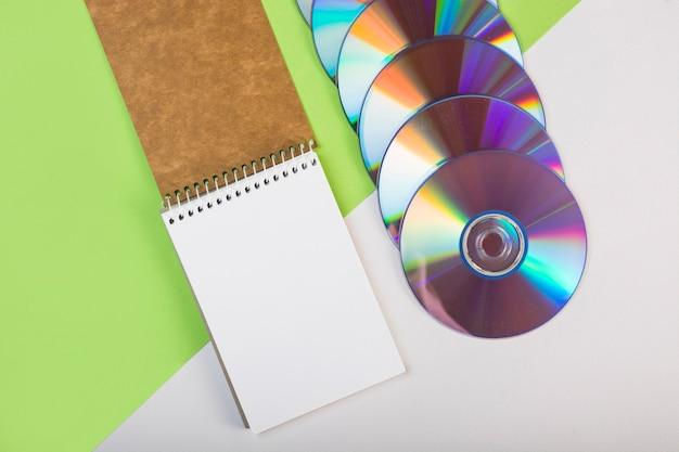 緑と白の二重の背景にカラフルなコンパクトディスクとスパイラルのメモ帳