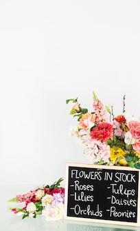 フラワーショップのガラスの机の上にストックの花を示すスレートのクローズアップ