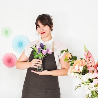 花の花瓶を保持している笑顔の女性の肖像