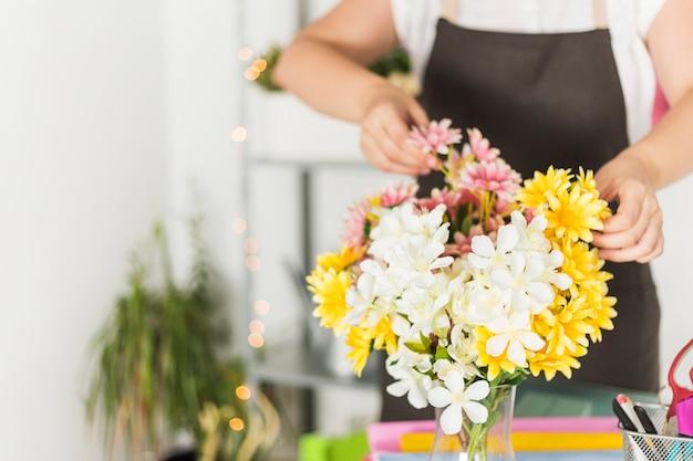 女性の花屋の前に新鮮な花のクローズアップ