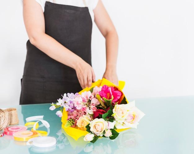 机の上に花の束を並べる花屋