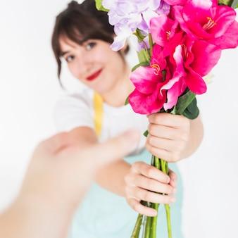 女性の花屋から花束を集める顧客