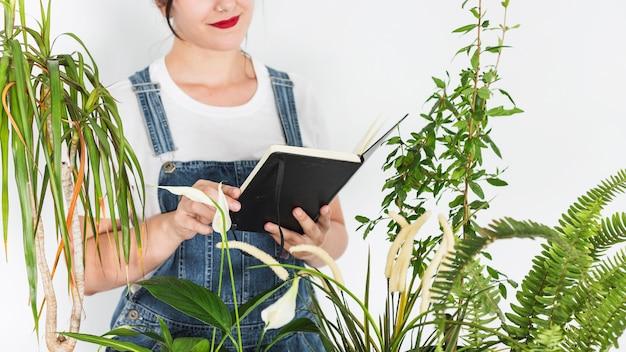 Женщина, держащая дневник возле растений