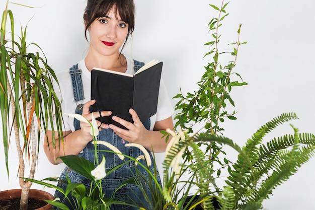 美しい女性の花屋の日記帳の前に鉢植えの植物