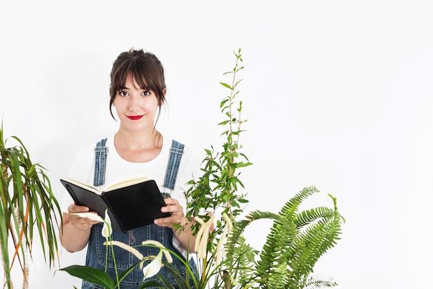 白い背景に日記を持っている女性の花屋の肖像