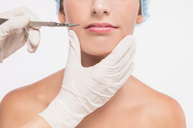 Доктор держит скальпель возле губ женщины
