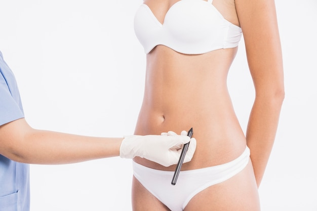 女性の体の近くに鉛筆を保持している外科医