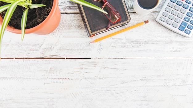 文房具や植物の近くの電卓やコーヒー