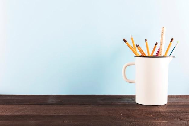 テーブル上に鉛筆と定規が付いているマグカップ