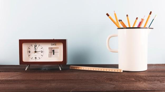 時計の近くのルーラーと鉛筆