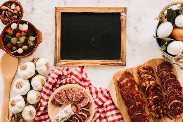 大理石のテーブルの上の黒板の近くの様々な食べ物