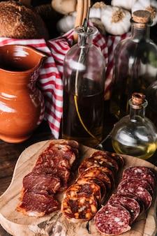Крупным планом колбасы возле масел и кувшинов