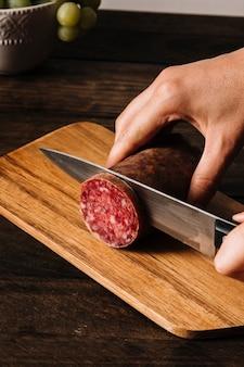 Обрезать руки нарезанной копченой колбасой на борту