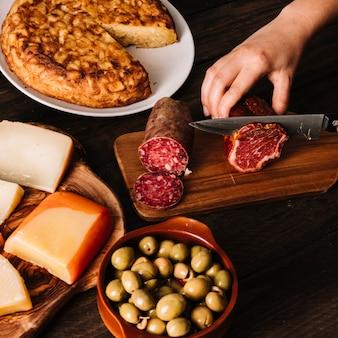 盛り付けた食べ物の近くでスモークした肉をスライスする手作り