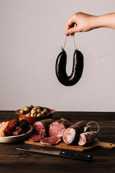 Кастрюля, держащая колбасу над едой