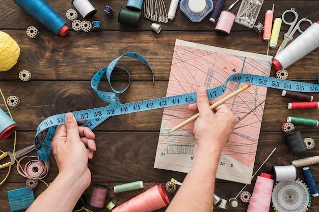 縫製物の近くのテープメジャーで手作業