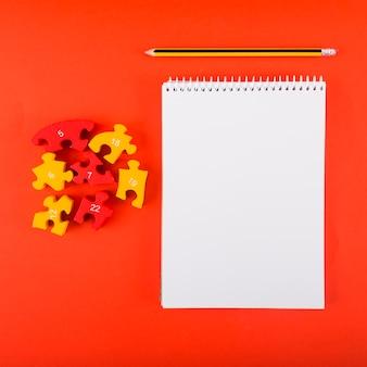 赤いテーブルにパズルを持つ空のノートブック