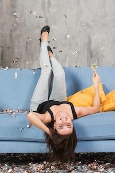 青いソファの上でシャンパンを持つ女性