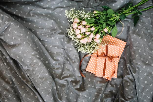 花束と贈り物はベッドの上に横たわる