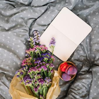 マカロンの近くの花とベッドのノート