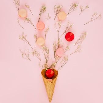 ワッフルコーンの近くの花とクッキー