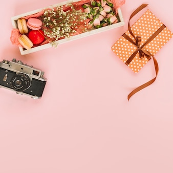 デザートの近くにプレゼントと写真のカメラ