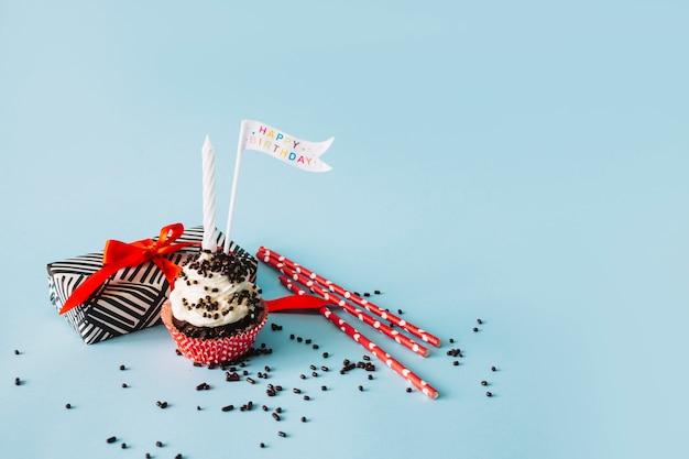カップケーキのそばのストローとプレゼント