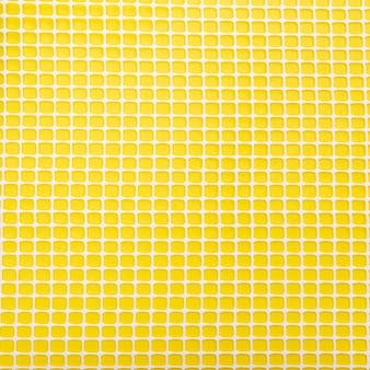 黄色の背景にプラスチックネット