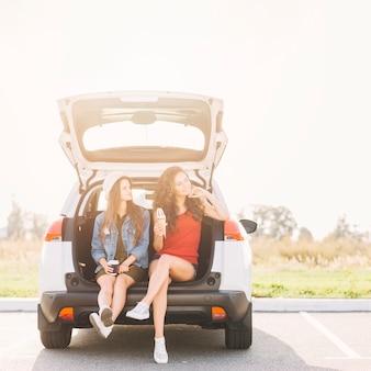 車のトランクに座っているかわいい女性