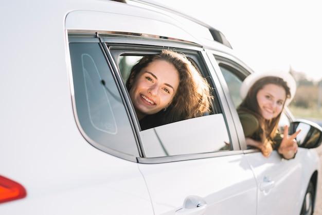 車の窓からぶら下がっている女性
