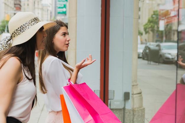 店の窓の近くのショッピングバッグを持つかわいい女性